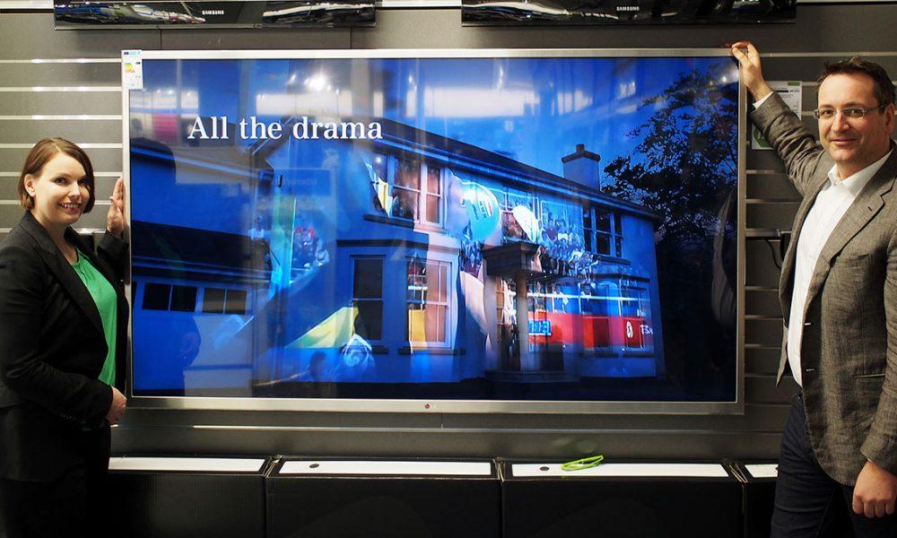 Kommunikasjonssjef Marte Ottemo og administrerende direktør Jan Røsholm i Stiftelsen Elektronikkbransjen blir små i forhold til LGs nye 84-tommers TV. (Foto: Stian Sønsteng/Elektronikkbransjen)